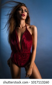Pretty woman in red bodysuit posing at camera against blue background