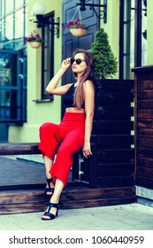 Pretty woman in red pants and sunglasses sitting outdoor
