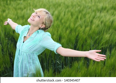 Pretty woman rejoicing in a green field standing with her arms spread wide open enjoying the beauty and tranquillity of nature
