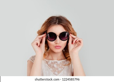 Pretty woman in round sunglasses smiling isolated light grey gray background holding her glasses puckering lips about to send a virtual kiss.