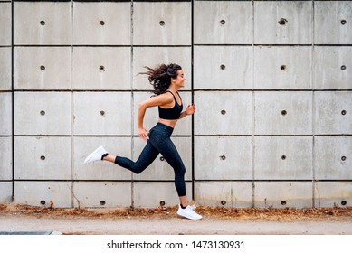 Pretty woman running together concrete wall.