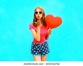 Pretty woman sends an air kiss holds a red balloon in the shape of heart on blue background