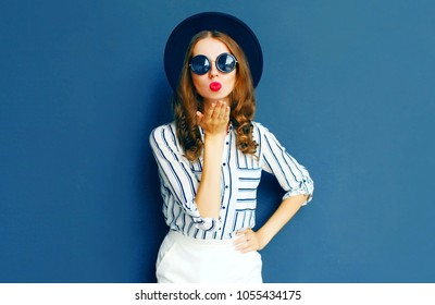 Pretty woman sends an air kiss wearing a black sunglasses, round hat and white skirt over a gray background