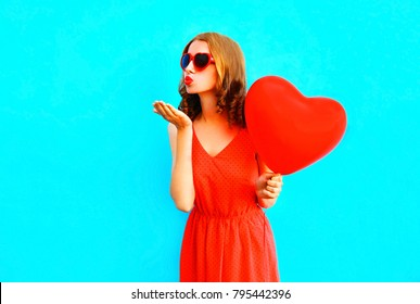 Pretty woman sends an air kiss with a balloons on blue background