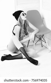 pretty woman or sexy cute girl with long blonde hair and adorable face in sunglasses, bra, hat, shoes and pants, sits at orange chair on white studio background