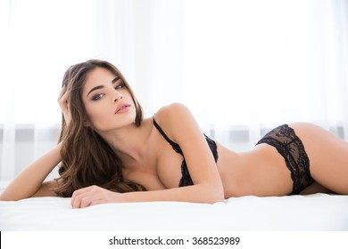 Pretty woman in sexy lingerie lying on the bed and looking at camera