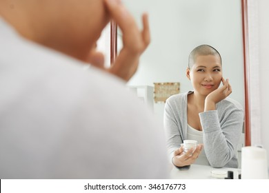Pretty woman with shaved head applying moisturizer in front of mirror