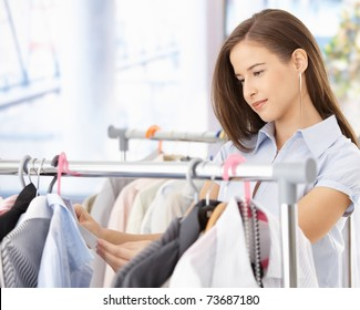 Pretty woman shopping clothes, looking at shirt price tag, smiling.?