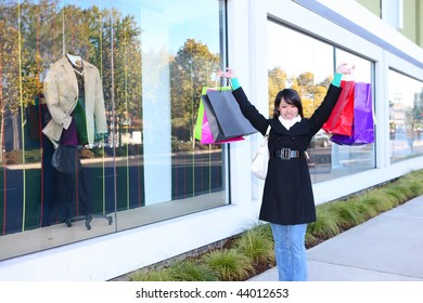 A pretty woman shopping with colorful bags walking to the next store