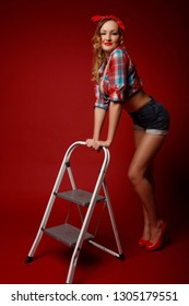 Pretty woman in shorts, red high heels, red bandana and decolletage colorful shirt stands with one foot on the ladder posing against red background. Full-growth retro-style pin-up portrait