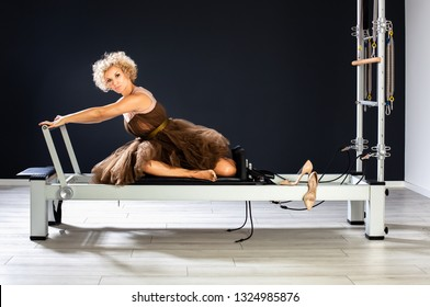 Pretty woman siting on tower reformer at the gym ready for the night out