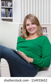 Pretty woman sits on an armchair with a notebook on her lap