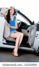 Pretty woman sits in the white car with door opened