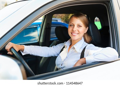 pretty woman sitting in the car and smiling