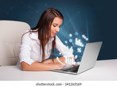 Pretty woman sitting at desk and typing on laptop with diagrams and graphs comming out