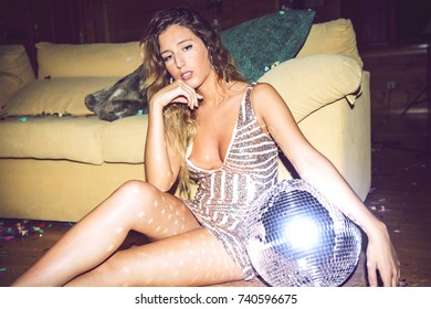 Pretty woman sitting with disco ball on floor covered with confetti and looking at camera.