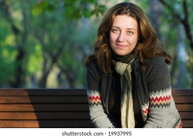 pretty woman sitting on a bench in park