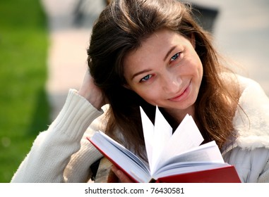 Pretty woman sitting on bench in park reading book smiling and looking into the camera