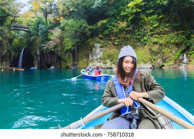 Pretty woman sitting on boat at takachiho gorge in Leaves color change season,Miyazaki,Japan