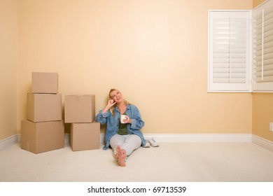 Pretty Woman Sitting on Floor with Cup Next to Moving Boxes in Empty Room.