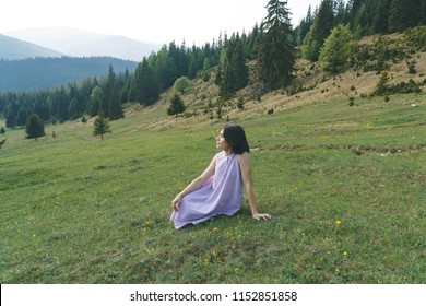 pretty woman sitting on grass and looking on pine forest