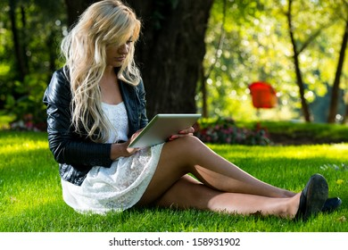 Pretty Woman Sitting On The Grass With Digital Tablet