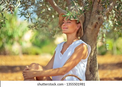 Pretty woman sitting and resting under the tree in the garden, enjoying nice warm spring day, spending leisure time outdoors, happy spring holidays