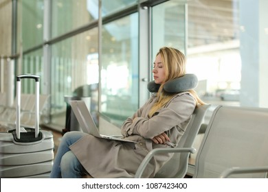 Pretty woman sitting in waiting room with laptop and using social networks near valise, using neck pillow. Concept of traveling and modern technology.