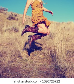 pretty woman in a skirt jumping up in cowboy boots in a wheat field on a hot summer day toned with a retro vintage instagram filter