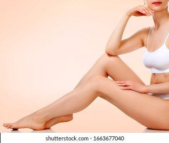 Pretty woman with slim beautiful body sitting against pastel background