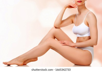 Pretty woman with slim beautiful body touching her smooth skin sitting against an abstract background with circles and copyspace.