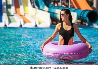 pretty woman with slim figure in black bikini holding rubber ring in the swimming pool. Summer Vacation. Enjoying suntan. Weekend on resort