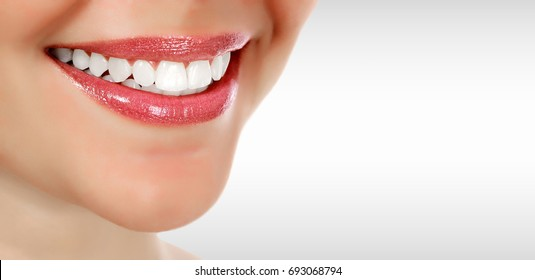 Pretty woman smiling against a grey background with copyspace. Closeup shot