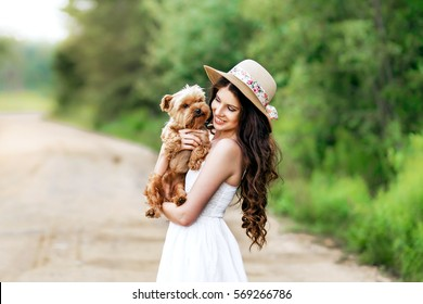 pretty woman smiling beautiful young happy with long dark hair in white dress holding small dog puppy yorkshire terrier