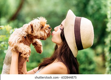 pretty woman smiling beautiful young happy with long dark hair in white dress holding and kissing small dog puppy yorkshire terrier