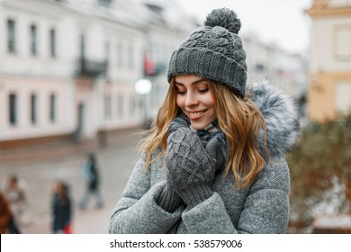 Pretty woman smiling in a knitted hat and a mittens on a background of the city.