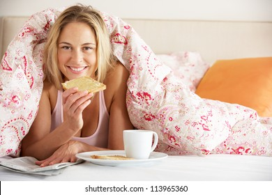 Pretty Woman Snuggled Under Duvet Eating Breakfast And Reading Newspaper