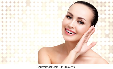 Pretty woman with soft and clear skin is posing against an abstract background with circles and copyspace