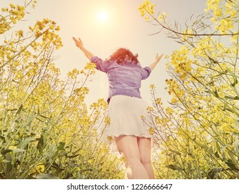 Pretty Woman standing back at the meadow with yellow flowers and raising hands up. Bottom view