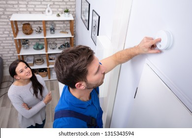Pretty Woman Standing Near Repairman Installing Smoke Detector On Wall At Home