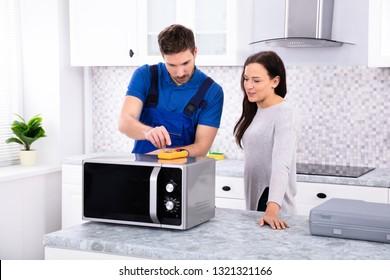 Pretty Woman Standing Near Repairman Repairing Oven Using Digital Multimeter In Kitchen