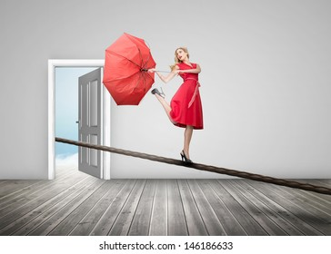 Pretty woman standing on a rope with a broken umbrella in an empty room