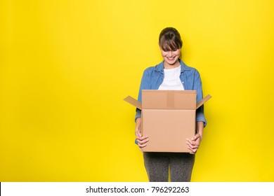 hübsche Frau auf gelbem Hintergrund mit bewegtem Karton