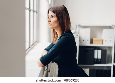 Pretty woman standing staring out of a window resting her arms on the sill with a serious pensive expression