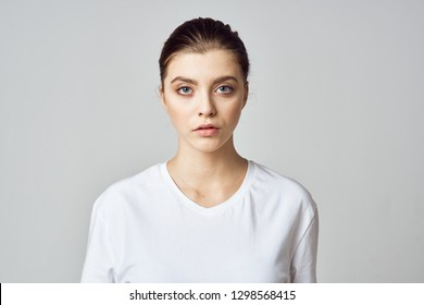 Pretty woman is standing in a white T-shirt on a gray background.