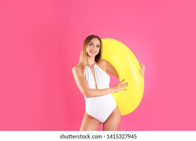 Pretty woman in stylish bikini with inflatable ring on color background