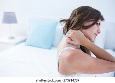 Pretty woman suffering from neck pain at home in the bedroom