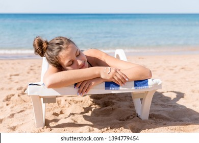 Pretty woman is sunbathing on the sunbed at the beach and has smiling face made of sunblock on her hand.