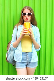 Pretty woman in sunglasses drinking fruit juice from cup over colorful green background