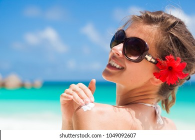 Pretty woman in sunglasses with red hibiscus flower in her hair putting sun cream on shoulder